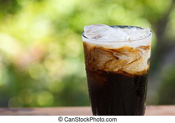 Iced coffee with milk on a wooden table.
