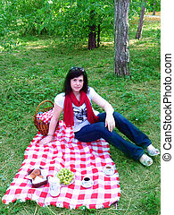 Picknick - Young woman on a green meadow on a picknick