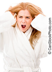 Young woman standing in bathrobe looking frustrated and...