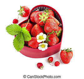 fresh strawberries in box as heart with green leaf