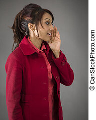 Side profile of an Indian young woman whispering - Adult...