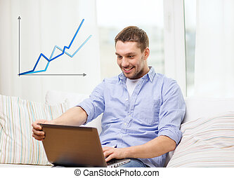 smiling man working with laptop at home - business,...