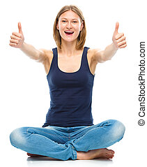 Young happy woman is showing thumb up sign - Young happy...
