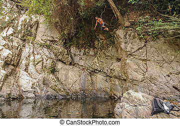 Man jumping over the abyss from a Cliff at Tayrona National...