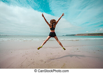 Young woman doing star jumps on the beach - A young woman is...