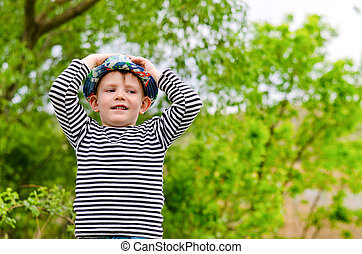 Happy little boy in a colorful blue hat standing with his...
