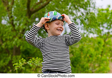 Jaunty macho little boy in a colorful trendy hat with a...