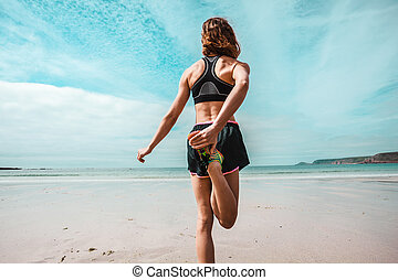 Athletic young woman stretching on the beach