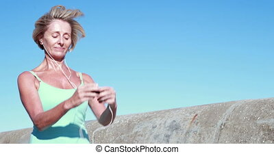 Fit senior woman pausing on her run to change her music on a...