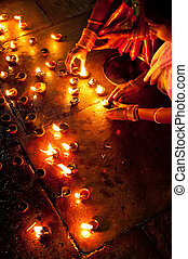 People burning oil lamps as religious ritual in Hindu temple...