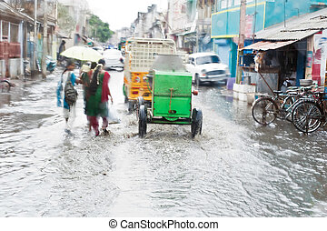Defocussed view of flash flood at Indian city street with...