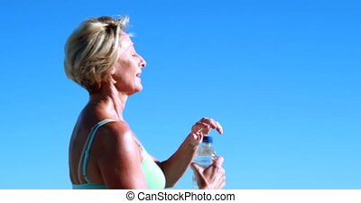 Fit senior woman pausing on her run to take a drink on a...