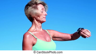 Fit senior woman pausing on her run to check her heartrate...