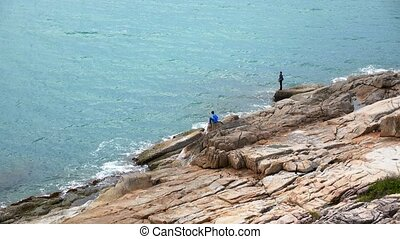 Men Fishing at the bottom of a Mountain. Rocky Dramatic Seascape.