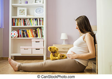 Pregnant woman with teddy bear - Portrait of beautiful...