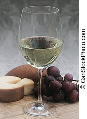 Wine With Grapes and Cheese - White wine in a glass with...