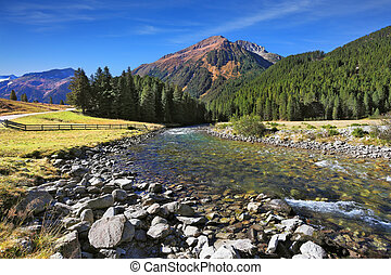 The river among green mountain meadows - Idyllic landscape....