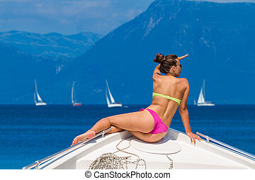 Young sexy woman on her private yacht with sailing yachts on...