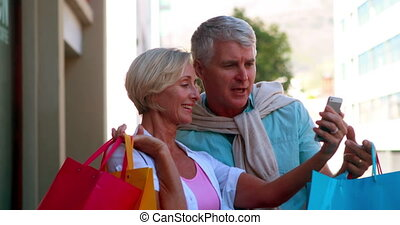 Happy couple on day out shopping looking at smartphone on a...