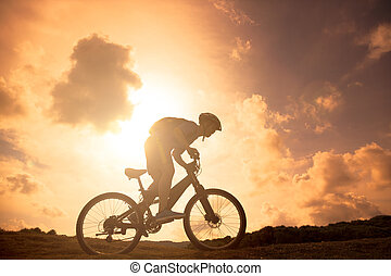 The silhouette of mountain bicycle rider on the hill