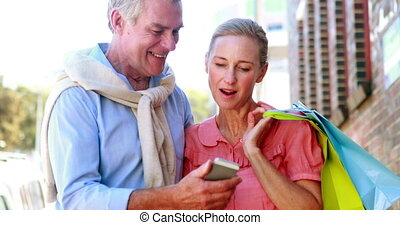 Happy couple looking at smartphone