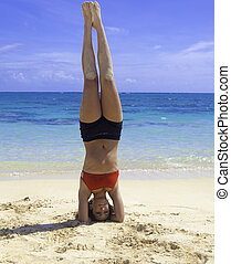 girl doing a headstand on the beach - girl in bikini doing a...