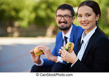 Having snack - Image of pretty businesswoman with sandwich...