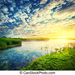 Landscape with a sunset sky and sun over a calm lake