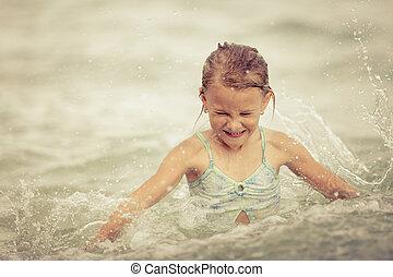 happy little girl splashing in the sea