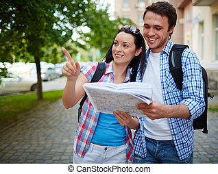 Modern travelers - Couple of travelers with map sightseeing...