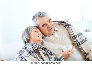 Warming up - Image of couple of pensioners having tea at...