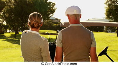 Couple standing on the golf course looking around on a sunny...
