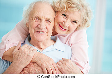 Embrace - Happy elderly couple hugging in front of the...