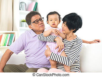 asian grand parents comforting their spoilt crying grand...