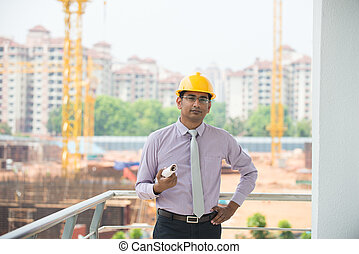 indian male engineer inspecting site with construction...