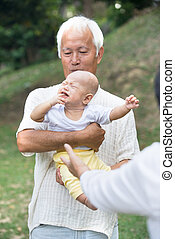 asian grandparents comforting crying baby grandson at outdoor