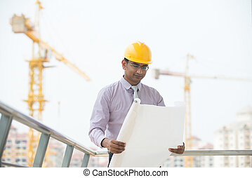 indian male engineer reading plans with construction...