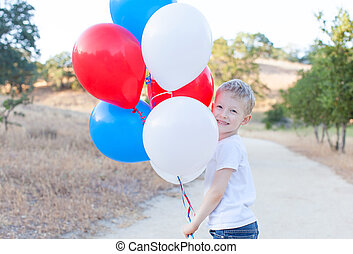 boy celebrating 4th of July - little cheerful boy holding...