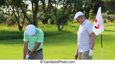 Man high fiving his friend after putting his golf ball on a...