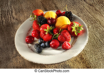 Platte with fresh fruits on a wood table