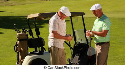 Two male friends chatting on the golf course by their kart...