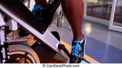 Fit man on the exercise bike at the gym