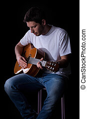 Man playing guitar - Portrait of a young man in casual...