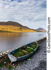 Overgrown rowboat at the shore of Kylemore Lough in Connacht