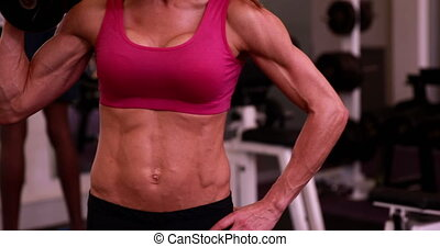 Super fit woman lifting dumbbells in pink sports bra at the...