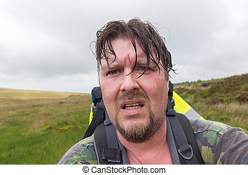 Man with wet hair and sweaty face looking exhausted and...