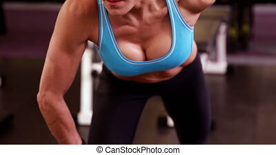 Fit woman lifting dumbbells at crossfit session at the gym