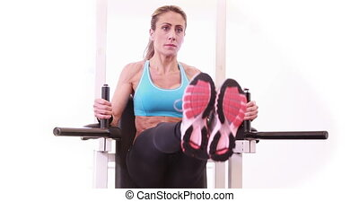 Super fit woman doing leg ups at crossfit session at the gym
