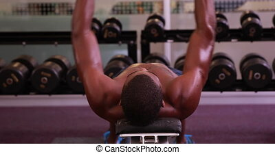 Fit shirtless man lifting dumbbells lying on bench at the...
