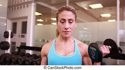 Super fit woman lifting dumbbells at crossfit at the gym